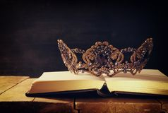 Low key image of beautiful queen/king crown over wooden table. vintage filtered. fantasy medieval period. Low key image of beautiful queen/king crown over royalty free stock photo