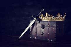 Low key image of beautiful queen/king crown and sword. fantasy medieval period. Low key image of beautiful queen/king crown and sword. fantasy medieval period royalty free stock images
