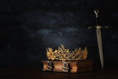 Low key image of beautiful queen/king crown and sword. fantasy medieval period. Low key image of beautiful queen/king crown and sword. fantasy medieval period royalty free stock image