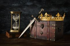 Low key image of beautiful queen/king crown, vintage hourglass and sword. fantasy medieval period. Low key image of beautiful queen/king crown, vintage royalty free stock photography
