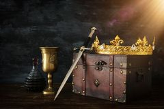 Low key image of beautiful queen/king crown, wine cup and sword. fantasy medieval period. Low key image of beautiful queen/king crown, wine cup and sword royalty free stock photo
