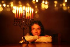 Low key image of jewish holiday Hanukkah background with cute girl looking at menorah & x28;traditional candelabra& x29;. And burning candles royalty free stock photos