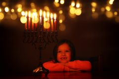 Low key image of jewish holiday Hanukkah background with cute girl looking at menorah & x28;traditional candelabra& x29;. And burning candles royalty free stock photo