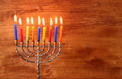 Low key image of jewish holiday Hanukkah background with menorah Burning candles over wooden background.  royalty free stock images