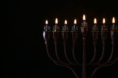 Low key Image of jewish holiday Hanukkah. Background with menorah (traditional candelabra) and burning candles Royalty Free Stock Images