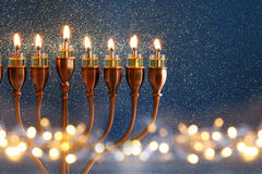 Low key Image of jewish holiday Hanukkah background. With menorah (traditional candelabra) and burning candles and glitter overlay Royalty Free Stock Photo