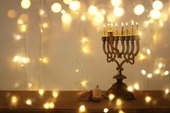 Low key image of jewish holiday Hanukkah background with traditional spinnig top, menorah & x28;traditional candelabra& x29;. And burning candles stock photo