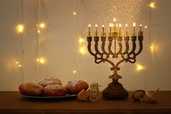 Low key image of jewish holiday Hanukkah background with traditional spinnig top, menorah & x28;traditional candelabra& x29;. And burning candles Royalty Free Stock Photography
