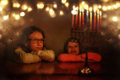 Low key image of jewish holiday Hanukkah background with two cute kids looking at menorah & x28;traditional candelabra& x29;. And burning candles royalty free stock image