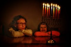 Low key image of jewish holiday Hanukkah background with two cute kids looking at menorah & x28;traditional candelabra& x29; Stock Photography