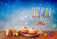 Low key image of jewish holiday Hanukkah with menorah, doughnuts and wooden dreidels (spinning top). retro filtered image.  stock photo