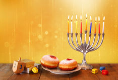 Low key image of jewish holiday Hanukkah with menorah, doughnuts and wooden dreidels (spinning top). retro filtered image Royalty Free Stock Photo