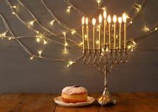 Low key Image of jewish holiday Hanukkah. With menorah (traditional Candelabra) and donut Stock Photos