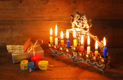 Low key image of jewish holiday Hanukkah with menorah (traditional Candelabra), donuts and wooden dreidels (spinning top) Royalty Free Stock Images