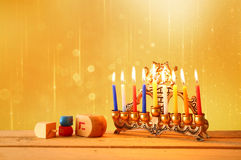 Low key image of jewish holiday Hanukkah with menorah (traditional Candelabra) and wooden dreidels (spinning top). glitter backgro Stock Photography