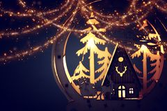 Low key Image of magical christmas scene of wooden pine forest, hut and santa claus over sleigh with deers. royalty free stock photos