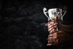 Low key image of a man holding a trophy cup over dark background. Low key image of a man holding a trophy cup over dark background royalty free stock photos