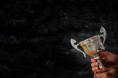Low key image of a man holding a trophy cup over dark background. Low key image of a man holding a trophy cup over dark background stock image
