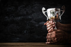 Low key image of a man holding a trophy cup over dark background. Low key image of a man holding a trophy cup over dark background stock photos