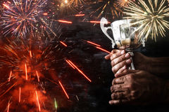 Low key image of a man holding a trophy cup over dark background. With fairworks overlay royalty free stock photos