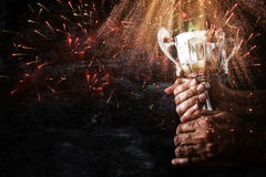 Low key image of a man holding a trophy cup over dark background. With fairworks overlay stock photography