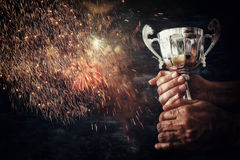 Low key image of a man holding a trophy cup over dark background. With fairworks overlay royalty free stock photo