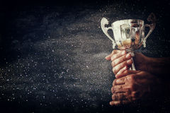 Low key image of a man holding a trophy cup over dark background. With glitter overlay royalty free stock image