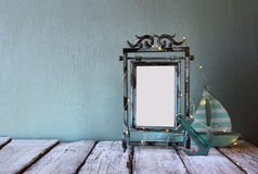 Low key image of old victorian steel blue blank frame with fairy garland lights Royalty Free Stock Photos