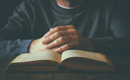 Low key image of person sitting next to prayer book.  Royalty Free Stock Image