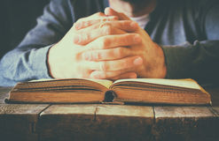 Low key image of person sitting next to prayer book Royalty Free Stock Image