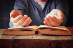 Low key image of person sitting next to prayer book.  Royalty Free Stock Images