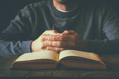 Low key image of person sitting next to prayer book.  Stock Photos