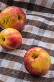 Low key image of red apples over wodden cotton  textured table Royalty Free Stock Images