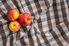 Low key image of red apples over wodden cotton  textured table Stock Photos