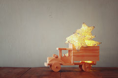 Low key image of retro wooden toy car with garland golden stars over wooden table. nostalgia and simplicity concept Royalty Free Stock Images