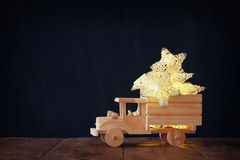 Low key image of retro wooden toy car with garland golden stars over wooden table. nostalgia and simplicity concept. Retro style image Royalty Free Stock Images