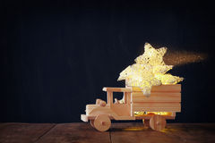 Low key image of retro wooden toy car with garland golden stars over wooden table. nostalgia and simplicity concept. Retro style image Stock Photo