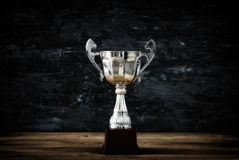 Low key image of trophy over wooden table and dark background.  royalty free stock photography