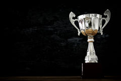 Low key image of trophy over wooden table and dark background.  stock image
