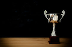 Low key image of trophy over wooden table and dark background.  royalty free stock images