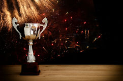 Low key image of trophy over wooden table and dark background. With abstract fireworks royalty free stock photography