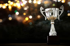 Low key image of trophy over wooden table and dark background. With abstract glitter lights stock photo