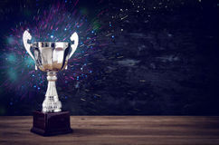 Low key image of trophy over wooden table and dark background. With abstract glitter lights royalty free stock photo