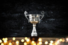 Low key image of trophy over wooden table and dark background. With abstract shiny lights royalty free stock photography