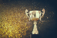 Low key image of trophy over wooden table and dark background. With glitter overlay stock image