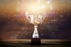Low key image of trophy over wooden table and dark background. With glitter overlay royalty free stock photos