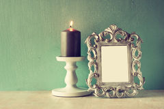 Low key image of vintage antique classical frame and Burning candle on wooden table. filtered image Royalty Free Stock Images
