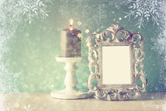 Low key image of vintage antique classical frame and Burning candle on wooden table and glitter lights background with snowflake Stock Photography