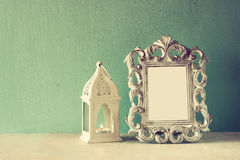 Low key image of vintage antique classical frame and Lantern on wooden table. filtered image. Royalty Free Stock Photo