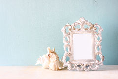 Low key image of vintage antique classical frame and Seashell on wooden table. filtered image Royalty Free Stock Photo